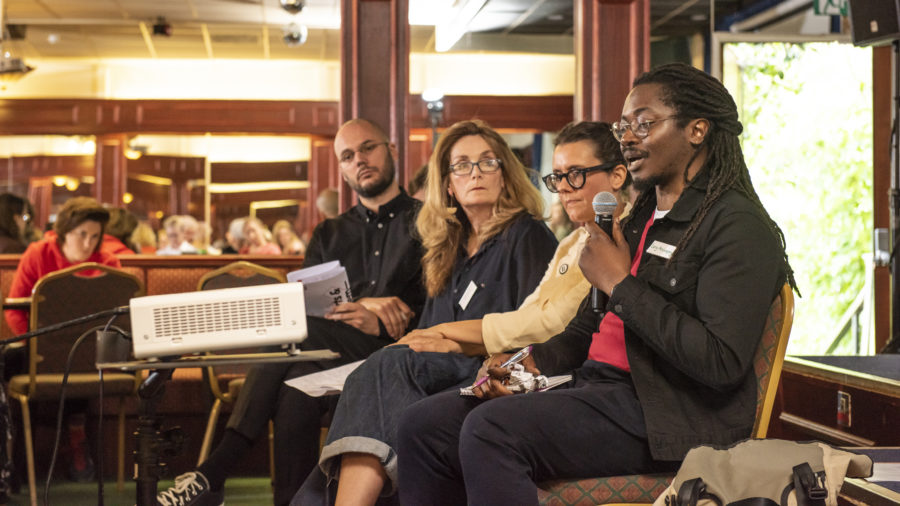 A black man with long braided hair and wearing glasses, a black jacket and trousers and red top, speaks into a microphone in a conference setting. At his side are three other panelists and an audience member can be seen watching.