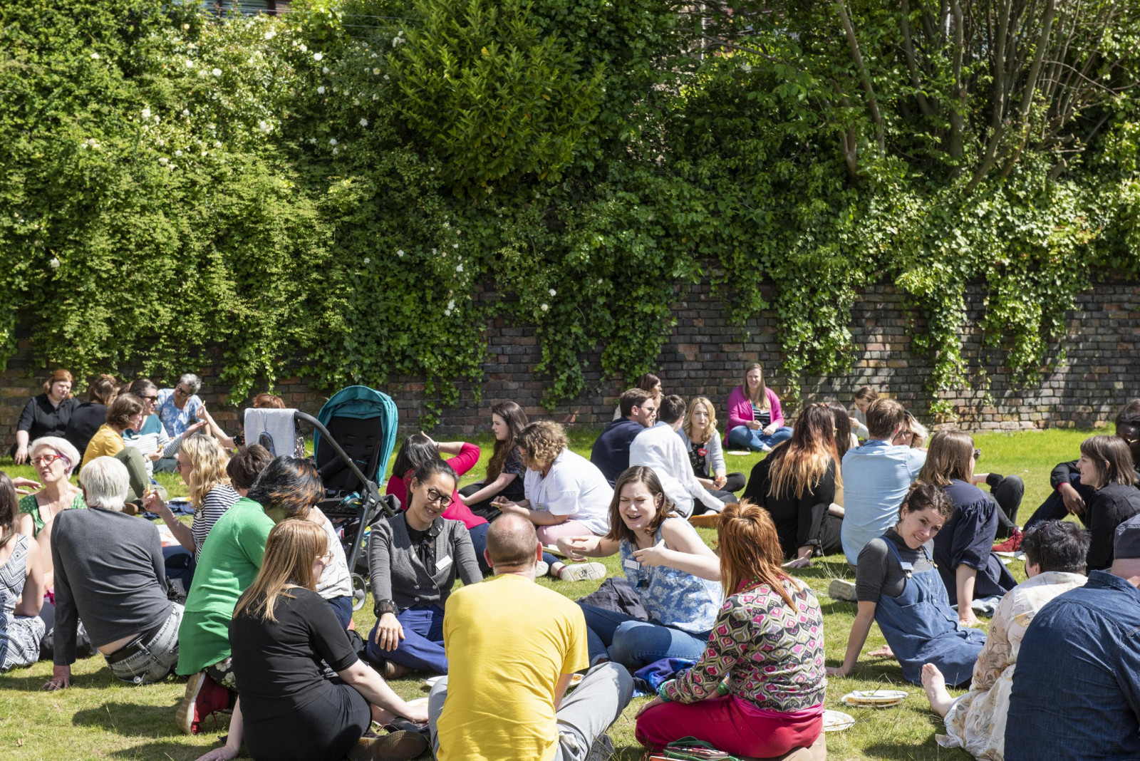In a large grassy, green space surrounded by trees is busy with people sitting in groups on the grass.