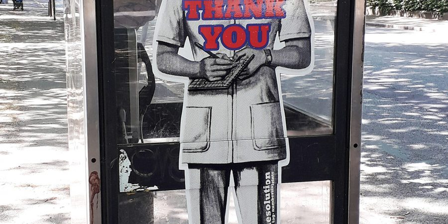 On the side of a phone box a black and shite image of a nurse covers the full height of the window with the words 'NHS Careers Thank You.'