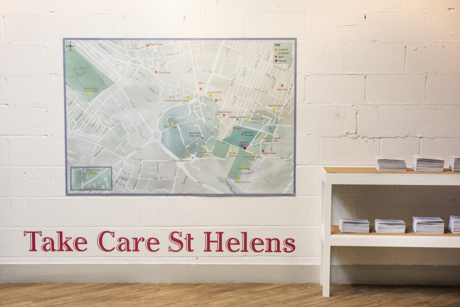 A large map hangs on a wall with a low set of shelves next to it with leaflets on top. Underneath the map the words 'Take Care St Helens' are printed in large red letters.