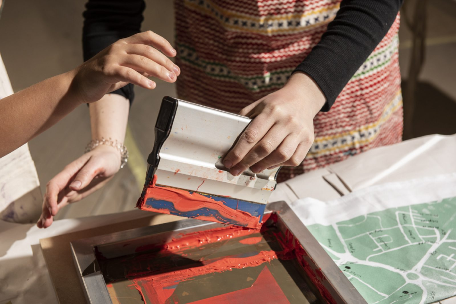 Two pairs of hands are screen printing. Next to the screen a piece of fabric with a map printed on it.