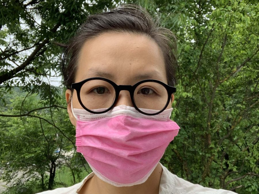 Artist Hwa Young stands against a backdrop of trees. They are wearing a pink medical mask.