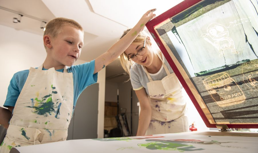 A young boy and a women are screen printing together. Both wear white aprons splattered with paint.