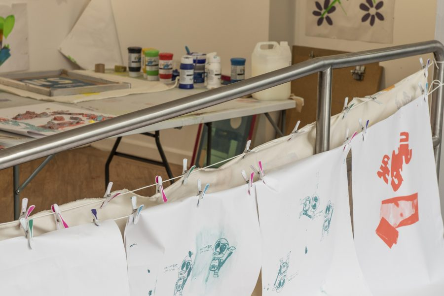A white room has a table with arts supplies and paper on. The room is full of screen printed posters hanging on the walls and on string.