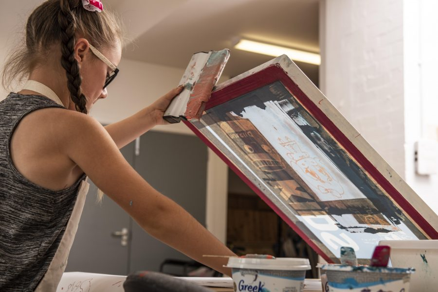 A young person with plaited hair holds a screen printing screen aloft and is surrounded by pots of paint.