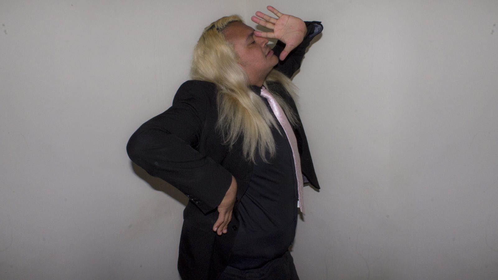 A young, light skinned man with long, blonde, wavy hair and brown eyes, wearing a black suit and shirt with a pink silk tie stands against a light grey background. He strikes a dramatic pose, facing the camera side on with one hand on his waist and the other against his face.