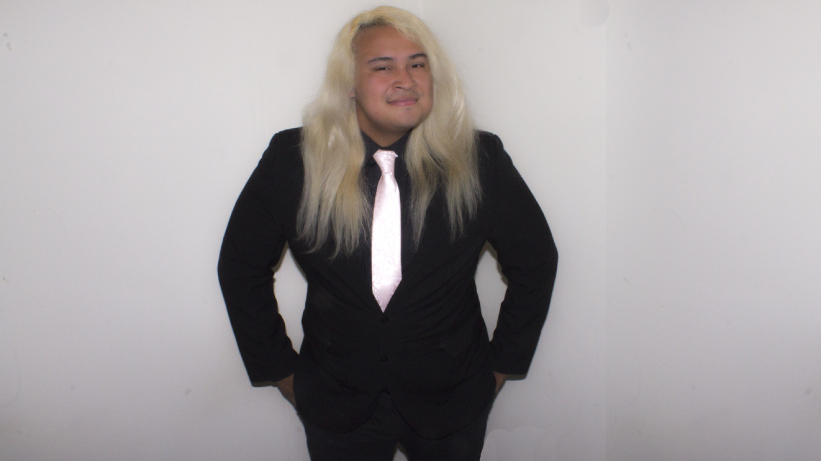 A young, light skinned man with long, blonde, wavy hair and brown eyes, wearing a black suit and shirt with a pink silk tie stands against a light grey background. He faces us with hands in trouser pockets, he has a content smile