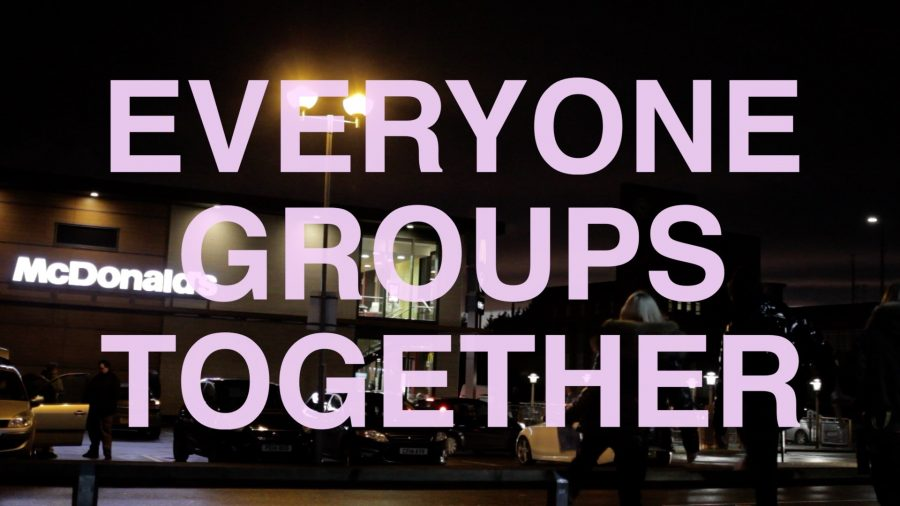 A photograph of a McDonalds with the words 'Everyone Groups Together' in large, lilac coloured capital letters.