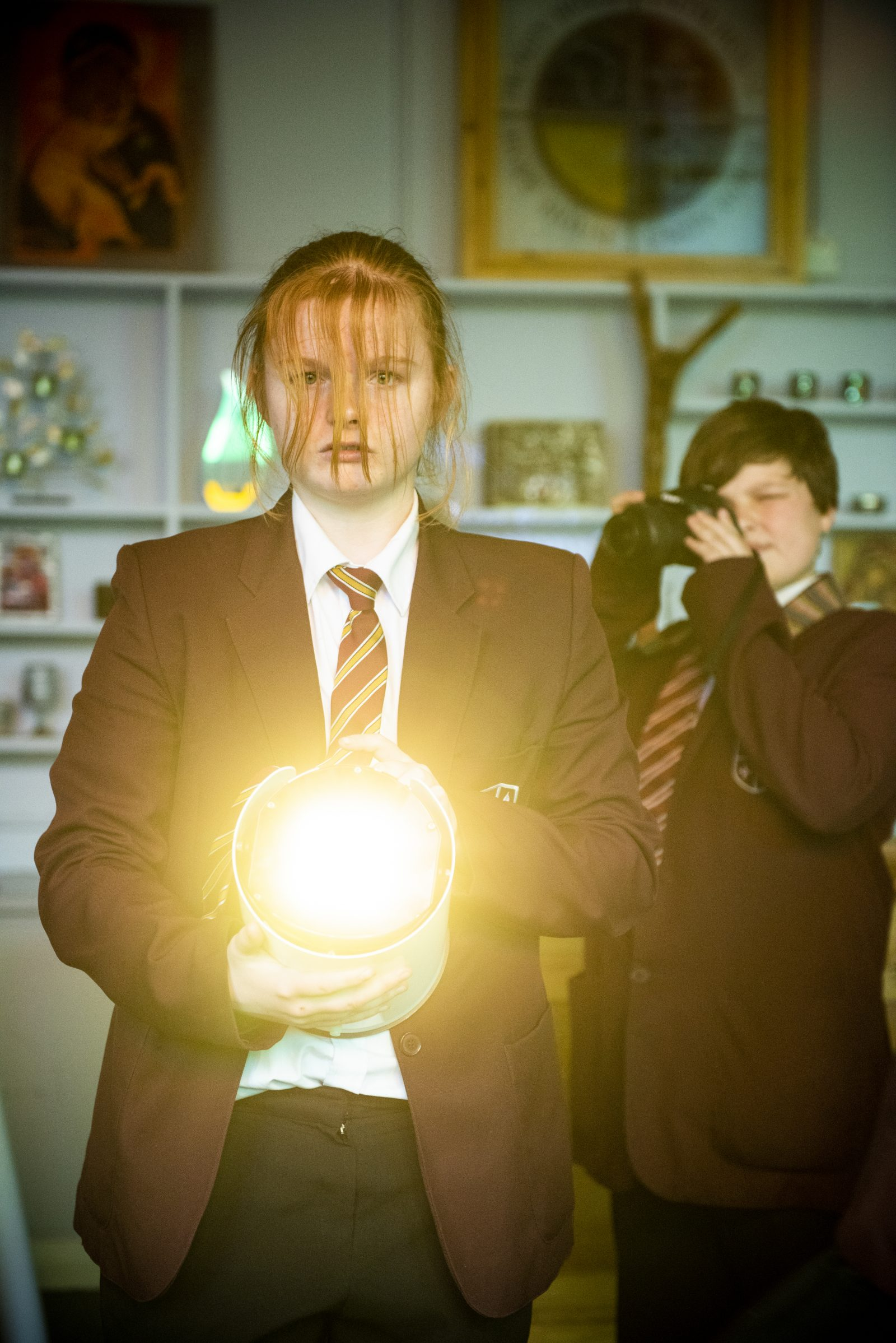 A young person in a school uniform is facing the camera, holding a large spotlight and shining towards us. They have long red hair which falls over their eyes and serious look on their face. Behind them another young person in a school uniform is holding up a camera and taking a picture.