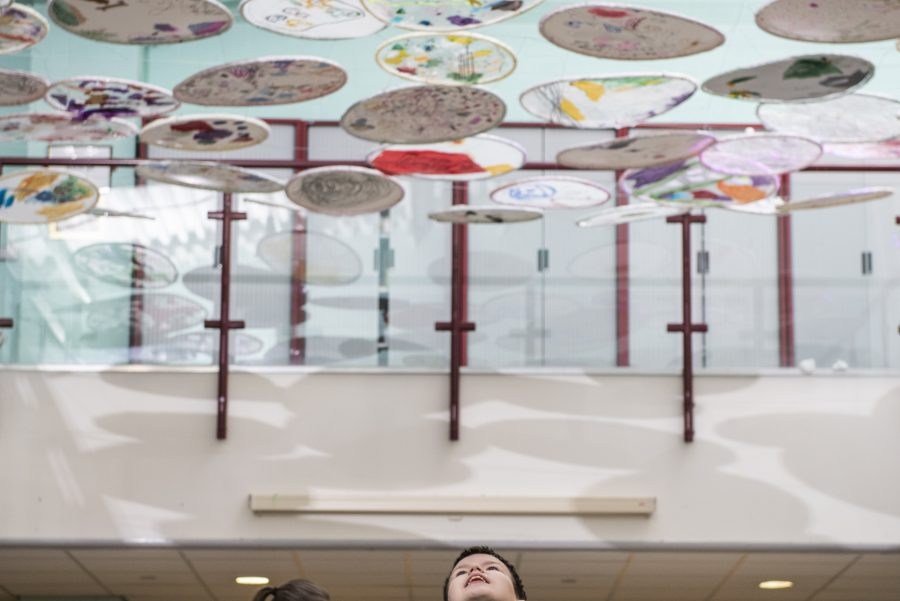 A canopy of circular artworks hangs above a room. Some of the circles are plain white, some have abstract, colourful designs. A young person stands underneath looking up towards the artworks. Some people are gathered in the background.