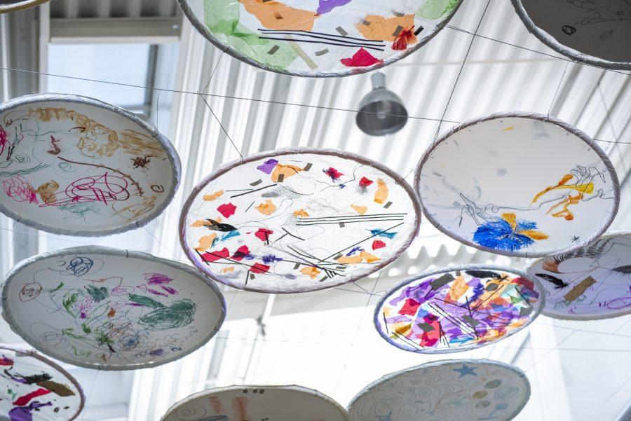 A canopy of circular artworks hang underneath a plastic ceiling. The artworks are colourful and abstract with light shining through from the ceiling.