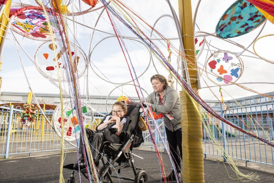 A woman in a stripy shirt is pushing a small girl in a wheelchair underneath a brightly coloured artwork made of streamers and hula hoops in a playground. The woman is smiling and the young girl is grinning.