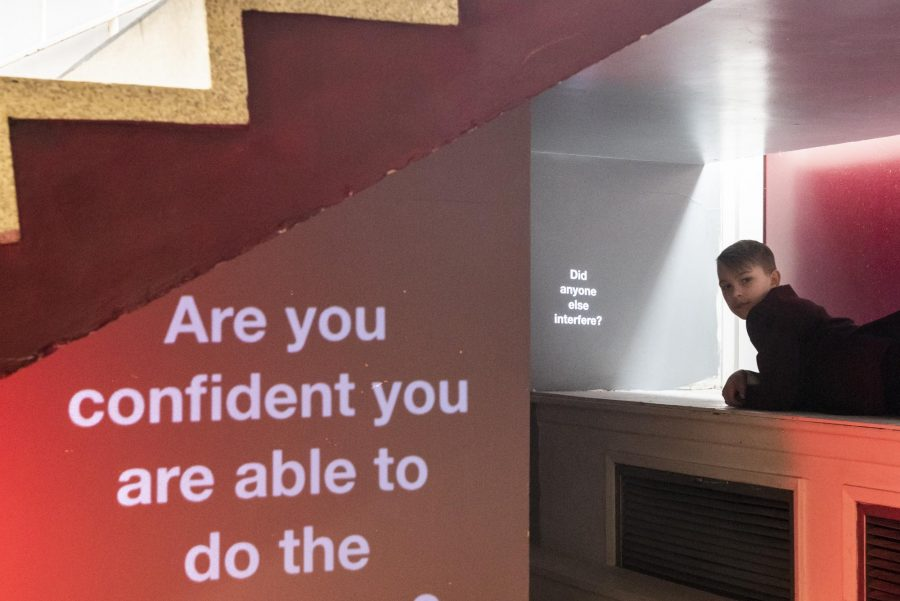 In a room with white walls, desk and stairs and a red carpet the words 'Are you confident you are able to do the right thing?' are projected on to a wall.