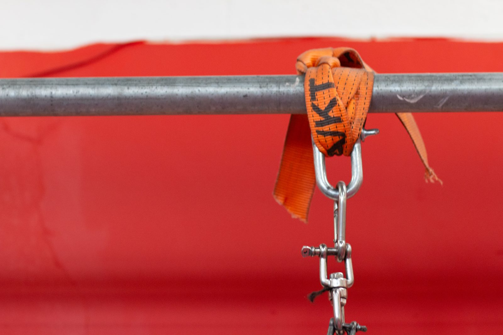 A metal bar against a red and white background. An orange strap is wrapped around the bar with a carabiner attached.