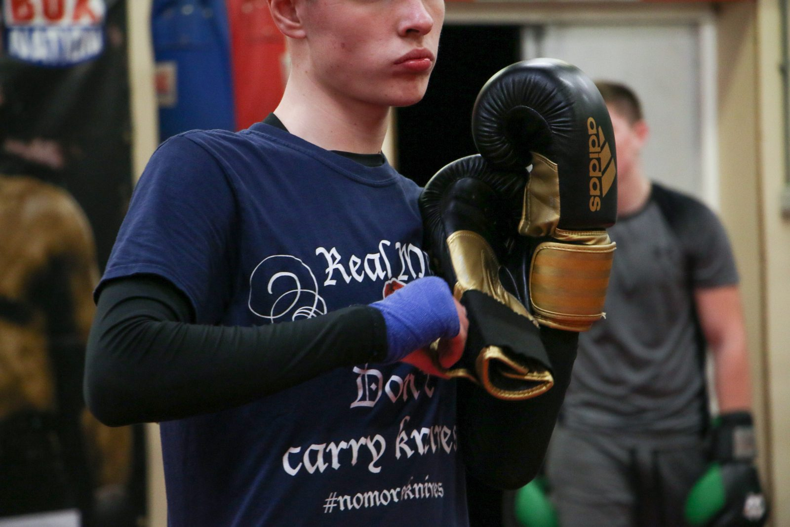 A person wearing a navy t-shirt and black long sleeved top pulls on a pair of black and gold boxing gloves.