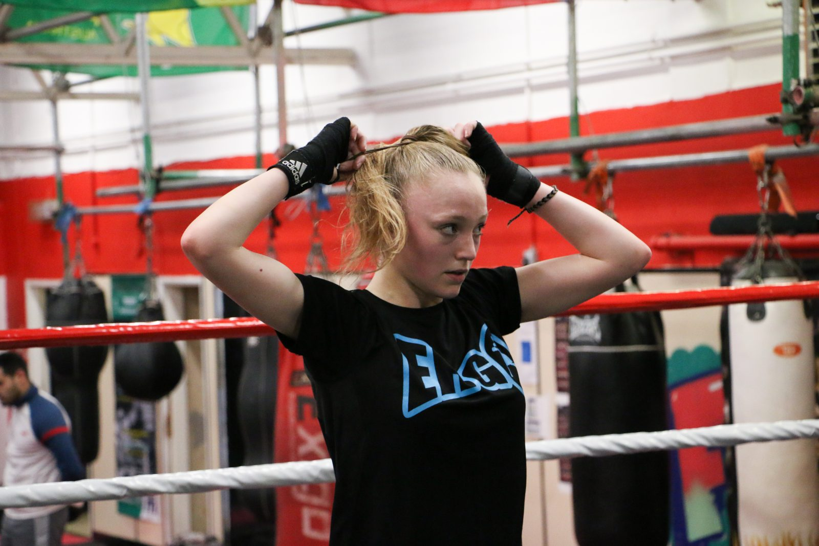 A young person with blonde hair wears a black t-shirt and thing black, fingerless gloves. They are tying their hair in a ponytail.