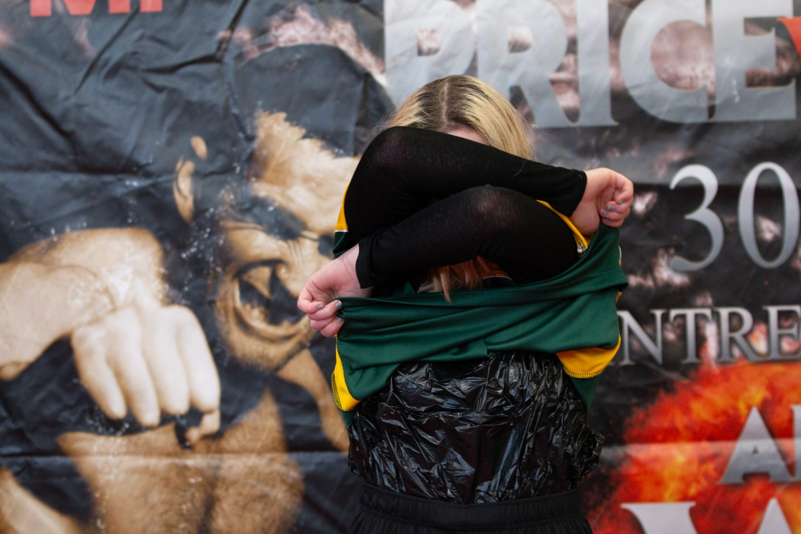 A person is removing a green and yellow sports top. They have a black long sleeved top underneath.