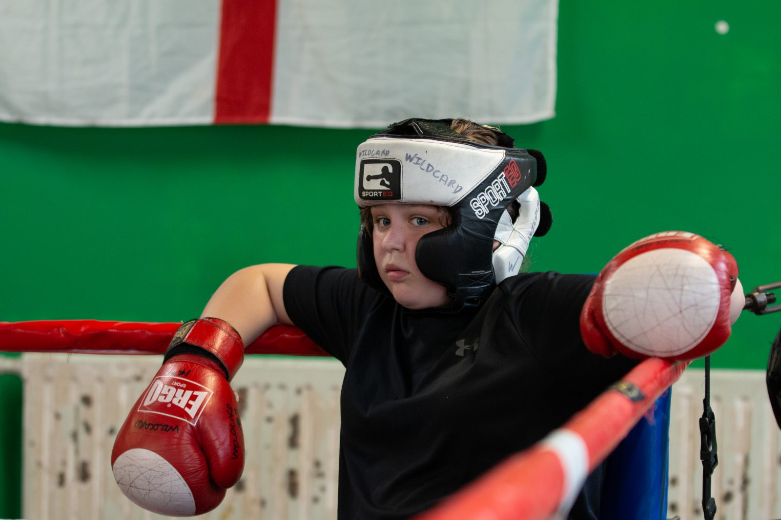 A young person leans against the inside corner of a boxing ring. They are wearing a black and white headguards and red and white boxing gloves.