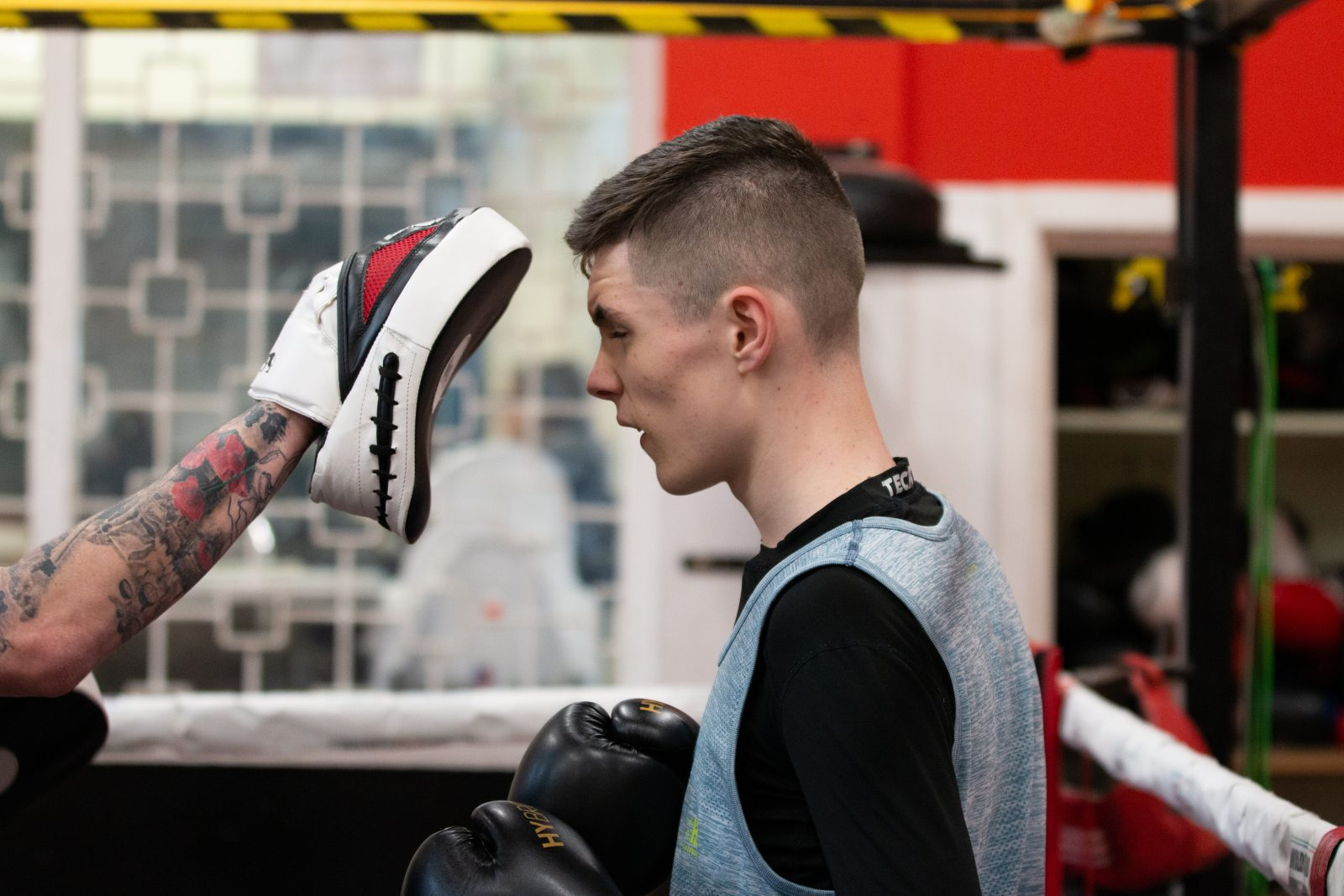 A young person wears a black long sleeve top, a blue sports vest and black boxing gloves. A tattooed arm holds a boxing pad close to their face.