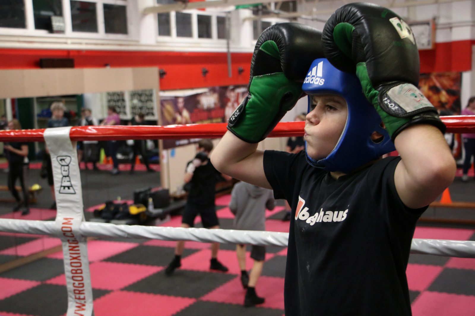 A young person wearing a blue boxing headguard and black and green boxing gloves holds their hands on top of their head in a boxing ring. In the background two people are boxing on a black and red chequered floor.