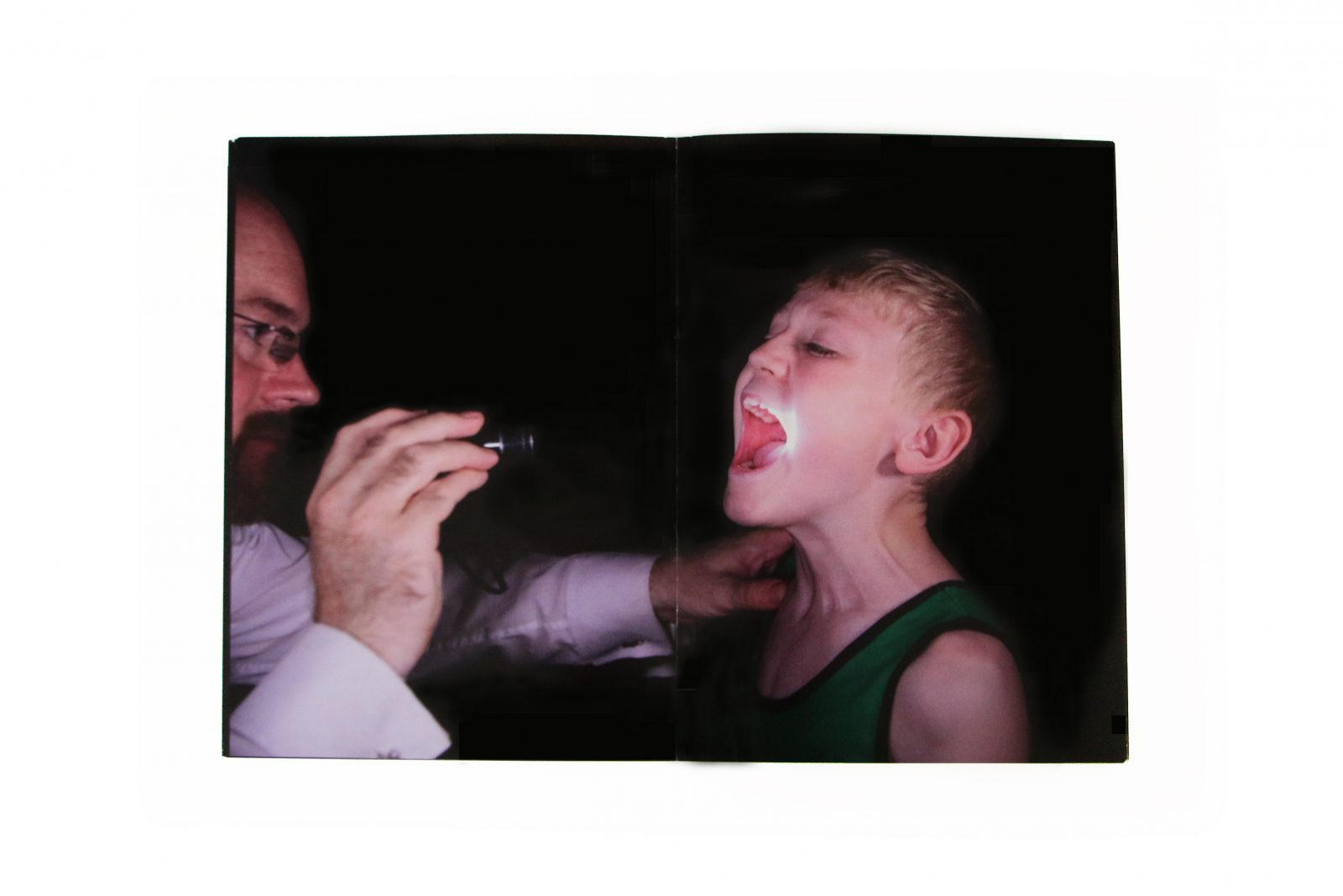 A man points a torch in to a young persons mouth.
