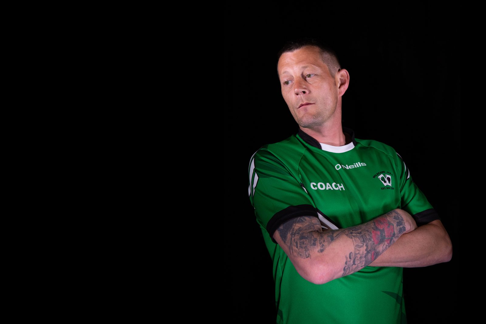 A man with tattoos on one arm, wearing a  green sports top stands with crossed arms and looks to one side.