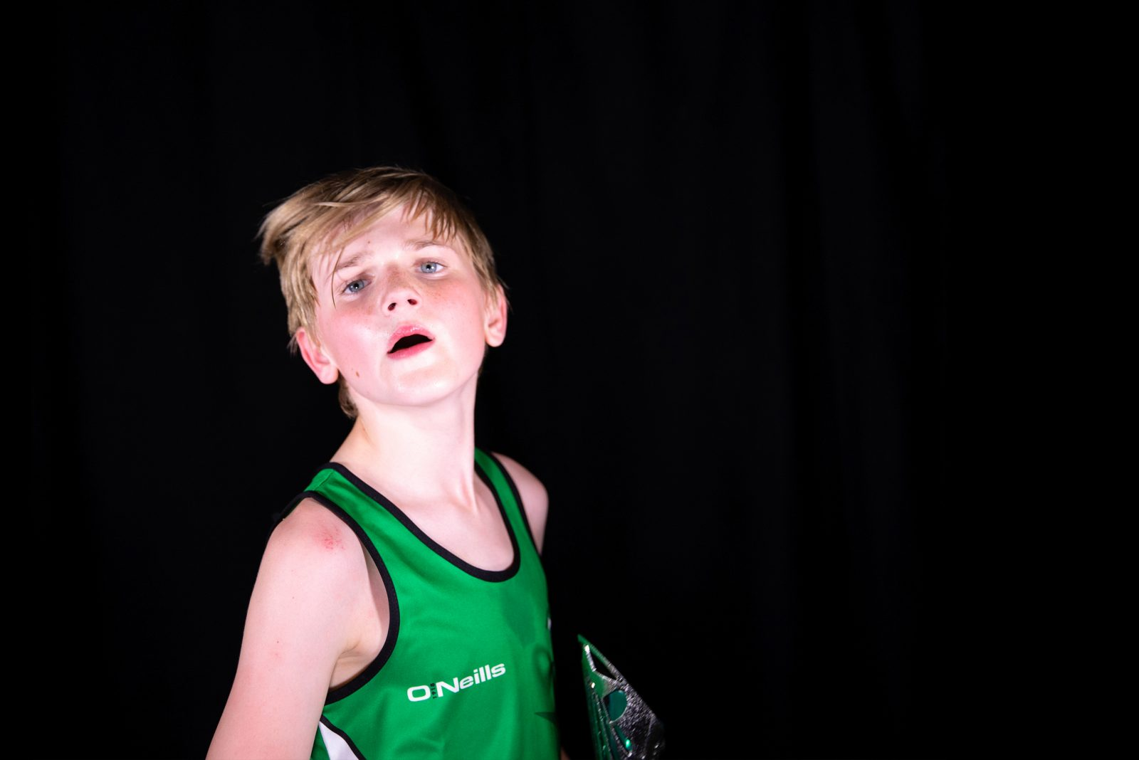 A young person with light hair, wearing a green sports vest looks as if they have just turned to look at the camera. They are red faced and sweaty.