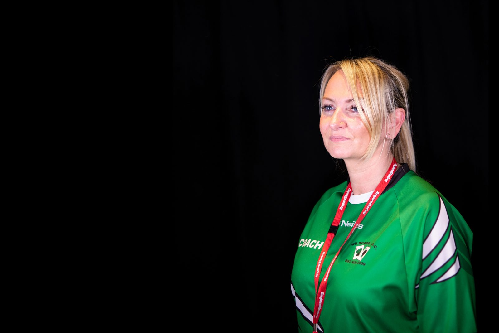 A woman in a green sports top and a red lanyard around her neck looks in to the distance and smiles.
