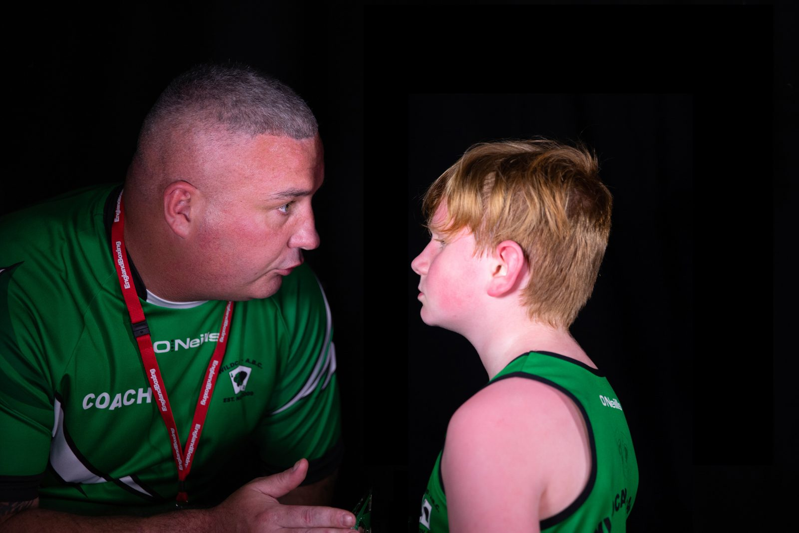 A man wearing a green sports top and a red lanyard is talking to a young person in a green sports vest. The man is gesturing with their hand. The young person is red faced,