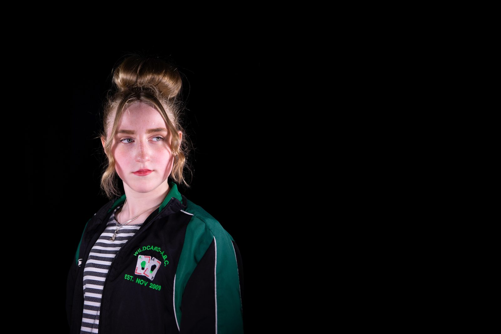 A young woman wearing a striped top and a black and green sports jacket stands a looks to one side.