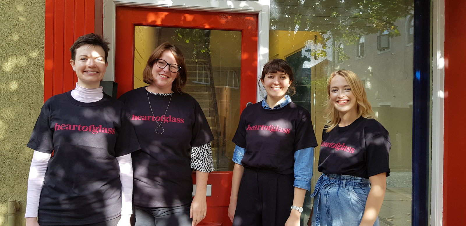 Four women stand in front of a building with a red door and woodwork and a large window. They are all wearing black tshirts with the red Heart of Glass logo printed on to them. This new logo is the words heart of glass across one horizontal line without spaces.