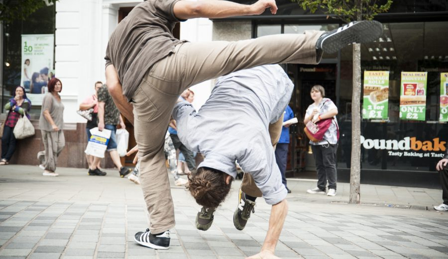 Two people dance on a high street. One is rolling towards the floor while the other swings their leg over the top of the other.