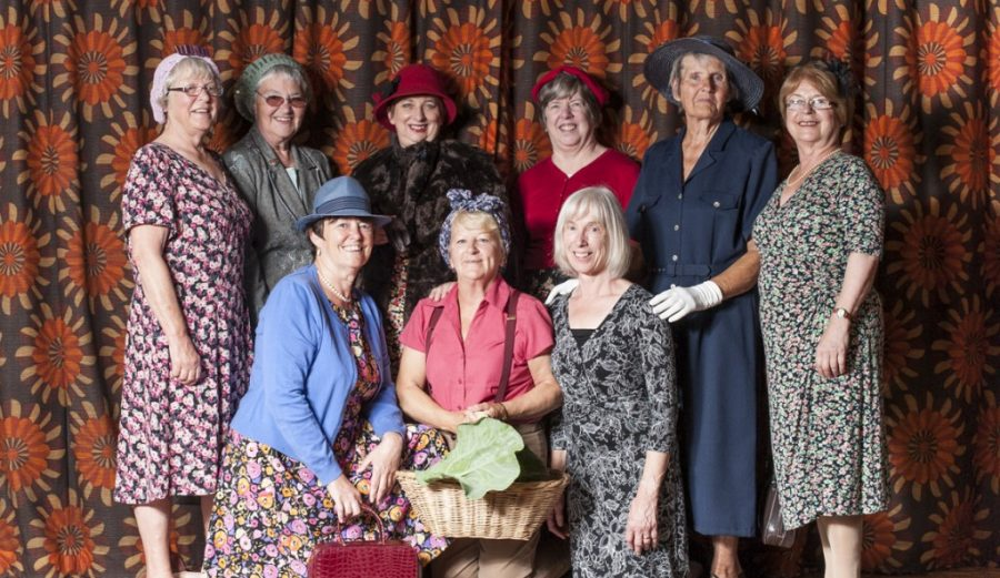 A group of people in vintage style floral dresses, and hats stand posed for a photograph in front of c colourful patterned curtain.