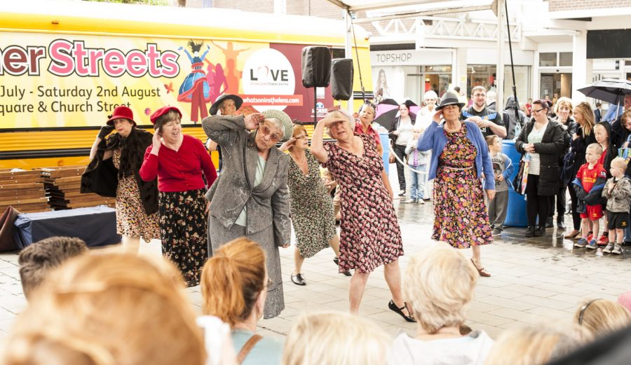 A group of people dressed in vintage style floral dresses, skirt suits and hats are dancing on a stage in front of an audience of people.