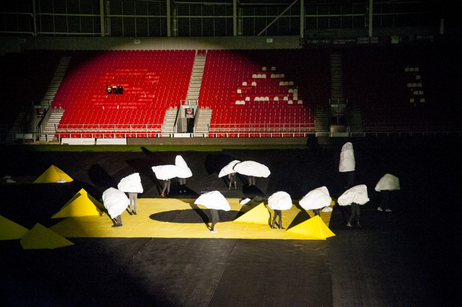 In a rugby stadium, with empty red seats behind them, a collection of large rock shaped sculptures with human legs move around the pitch which is covered in black material and had yellow sculptures on the ground. They are lit by a spotlight.