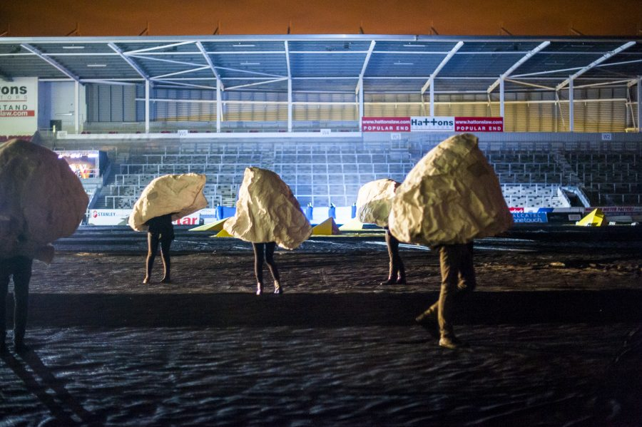 Five rock shaped sculptures with one person in each stand with their legs visible in an empty rugby stadium. It is night time and the pitch is lit by flood lights.