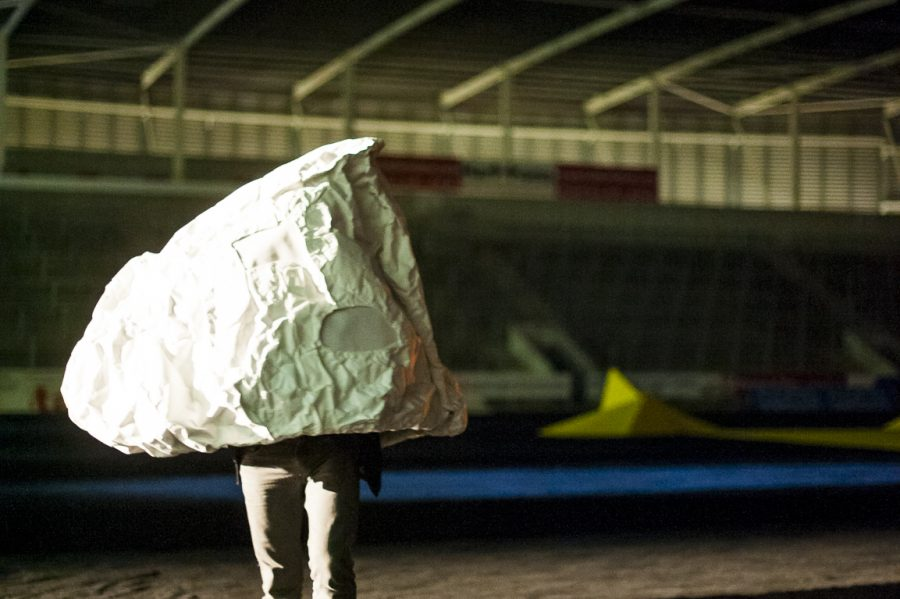 In a rugby stadium a large rock shaped sculpture has a person inside it with their legs visible. Under a night sky they stand on the pitch, which is covered by black material.