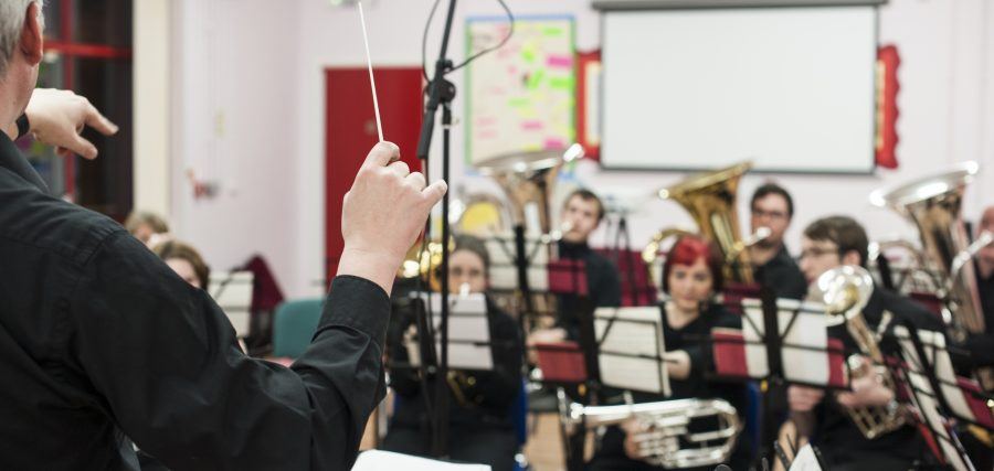 An over the shoulder view of a person with short, light hair earing a black shirt. The person had a conductor's baton in one hand and is pointing with the other. They are conducting a brass band. The brass band are wearing all black and are seating behind music stands in a bright room. Behind them is a whiteboard and red door.