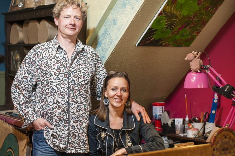 Two people smile towards the camera. One is standing up and has short, light curly hair. They are wearing a patterned shirt. The other is sat down. They have shoulder length, dark, straight hair and wear a denim jacket and large earrings. The person standing has their arm around the shoulder of the person sitting. They are surrounded by colourful paintings and art materials. They are behind a wooden desk which has a red pattern painted on top.