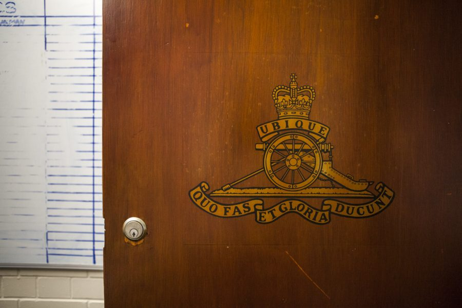 A crest painted in yellow gold on a wooden door.