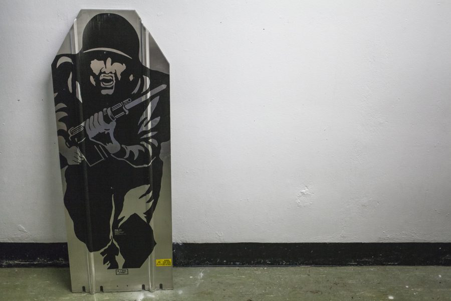 A piece of metal leans against a white wall. The metal is painted with a stencilled painting of a person in uniform charging with a gun.