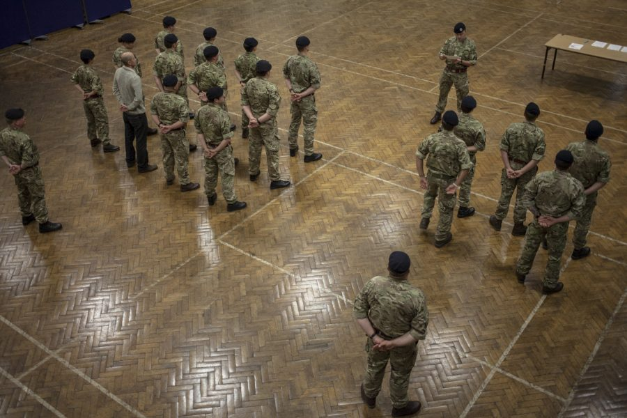 A group of people stand in army uniform in a large hall. They are being addressed by one person in uniform at the front.