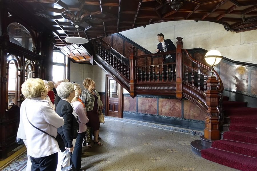 A group of people stand in a room ornate tiles floors and walls and a dark wood panelled ceiling. In the room is also a large, dark wood staircase with dark red carpet. On the staircase a man in a dark suit leans over the rail talking to the group of people.