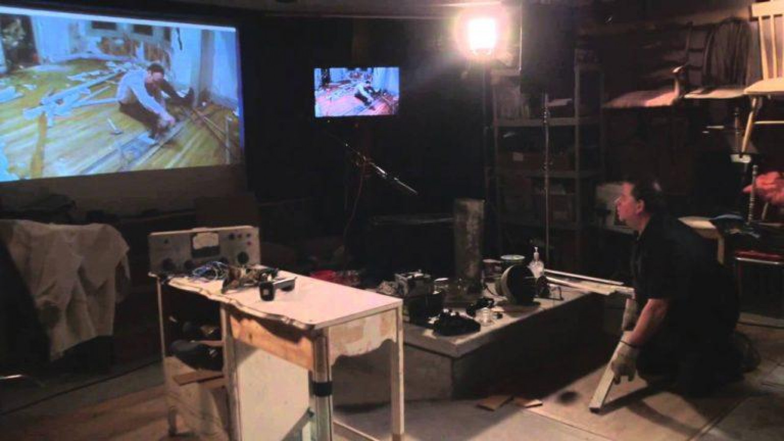An image of a person kneeling in a dark room, lit by one lamp. They are surrounded by camera and other visual imagery kit and are looking at a projector screen and TV with an image of a person sitting on a wooden floor.
