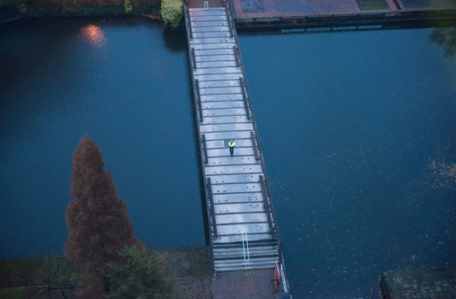 An aerial view of a person in a high visibility jacket walking across a bridge in evening light. The bridge crosses a body of dark, navy water, reflecting the evening sky.