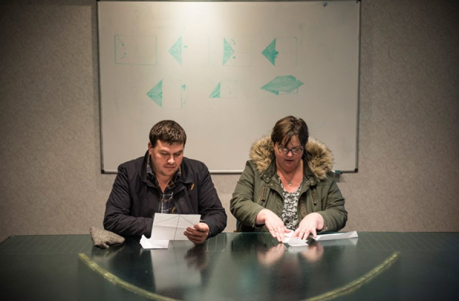 Two people sit at a table wearing coats. One of them reads from a piece of paper and the other is folding a piece of paper.