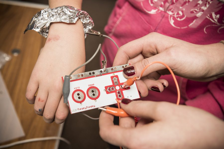 A young person's wrist has foil wrapped around it with wires attached. Another person in holding a control panel with buttons and wires attached.
