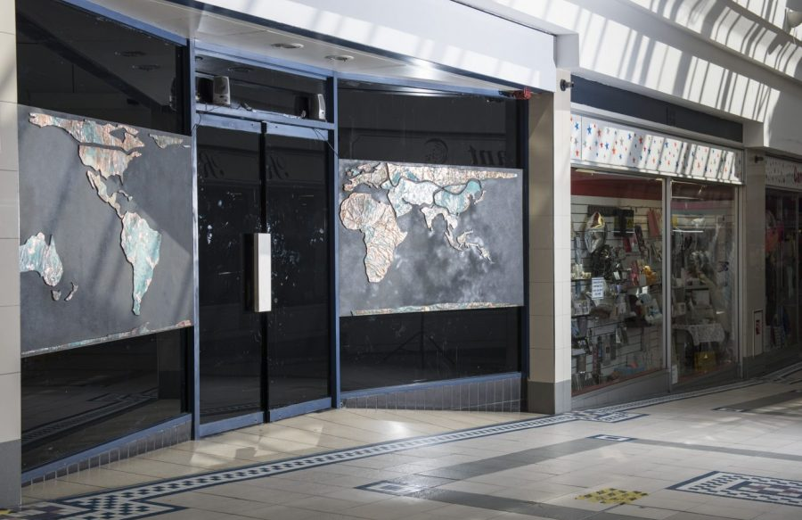 A shop window inside a shopping centre. On the window are two maps. The windows and doors are otherwise blacked out.