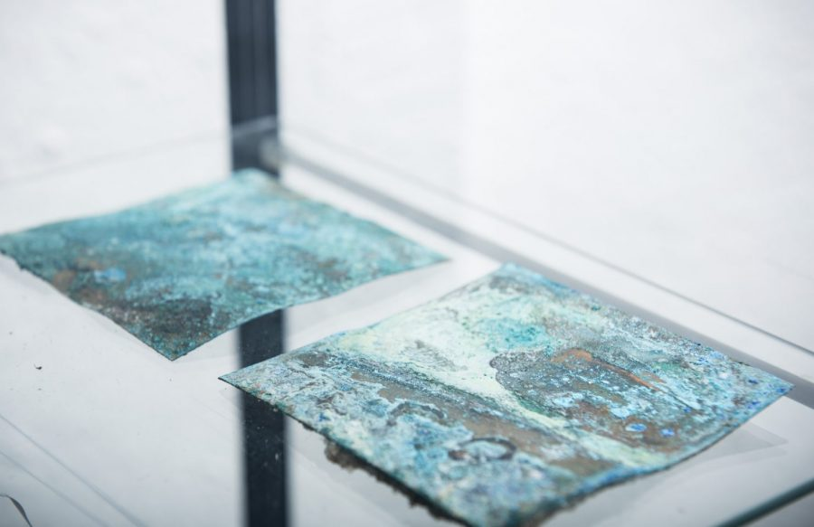 Two pieces of metal with green, blue and white patterns on them.