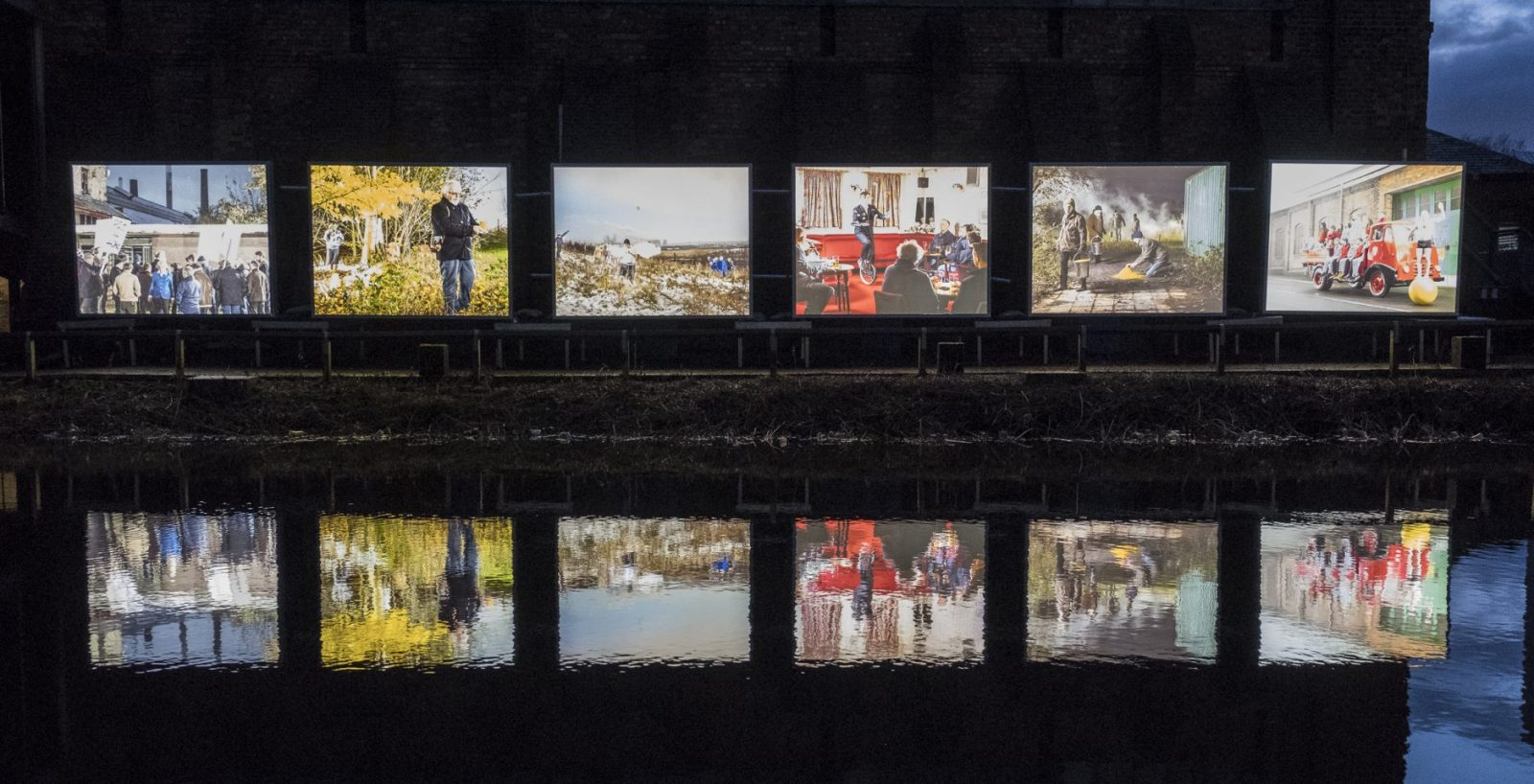 6 large light boxes with a different image in each stand in a row next to a canal. The canal water reflects the images. It's dark outside.
